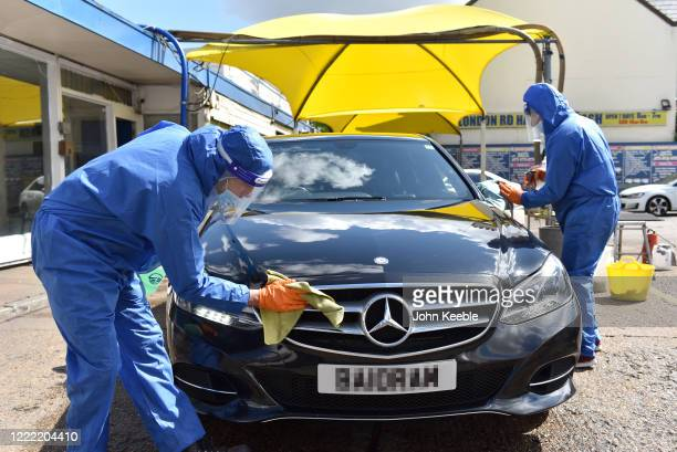 Workers wash cars wearing full protection against Coronavirus operating social distancing measures and is currently only washing exteriors of...