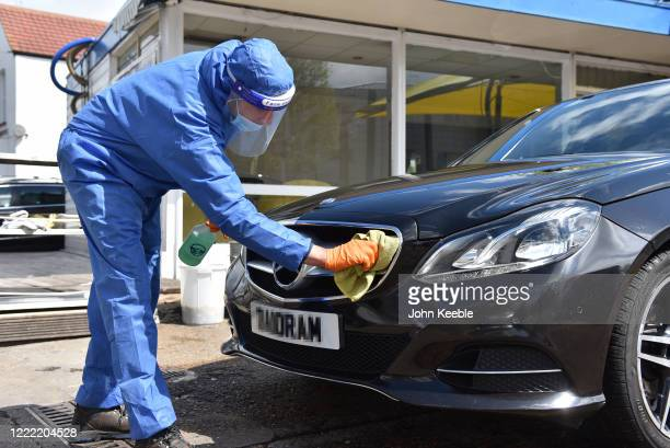 Workers wash cars wearing full protection against Coronavirus, operating social distancing measures and is currently only washing exteriors of...