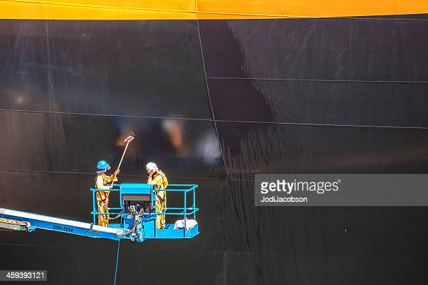 Workers washing the side of a cruise ship