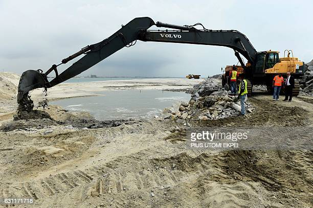 Workers watch a caterpillar digging a drainage at the planned Eko Atlantic City, Lagos, on November 22, 2016. With frozen cranes, deserted...