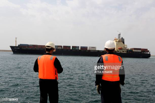 Workers watch a ship as it sails during an inauguration ceremony of new equipment and infrastructure at Shahid Beheshti Port in the Southeastern...