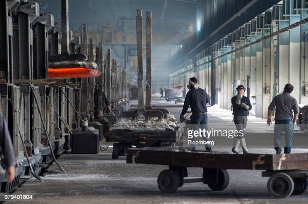 Workers watch as a lift loads a cart with heated aluminium ingots at the Iran Aluminium Co plant in Arak Iran on Tuesday June 19 2018 As OPEC oil...
