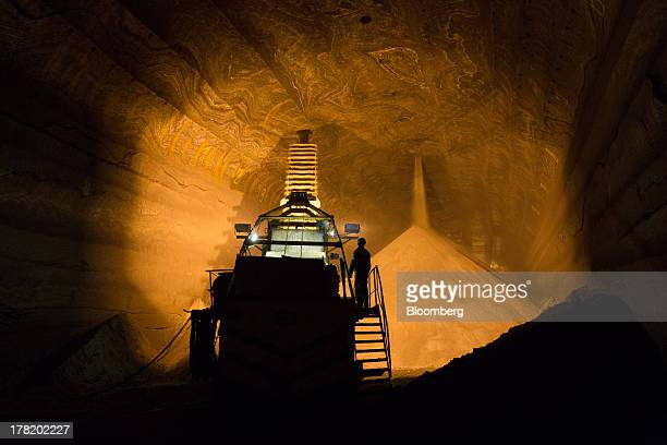 Workers watch as excavated potash pours from the tunnel ceiling into an underground storage area at a potash mine operated by OAO Uralkali in...