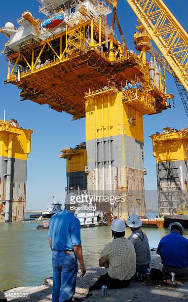 Workers watch as the hull of the Independence Project's hub is pulled into place to be connected to its topside at Kiewit Offshore Services in...