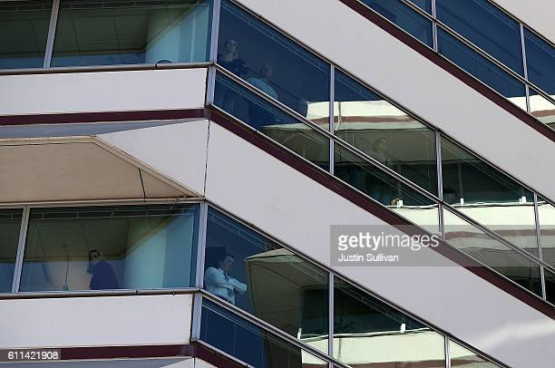 Workers watch from the windows of an office building as Democratic presidential nominee former Secretary of State Hillary Clinton speaks during a...