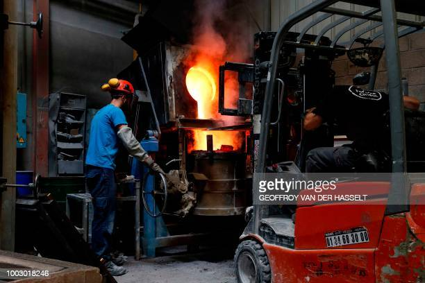 Workers watch the melting of bronze ingots at the Chapon Art Foundry on June 21 2018 in Bobigny a suburb north of Paris