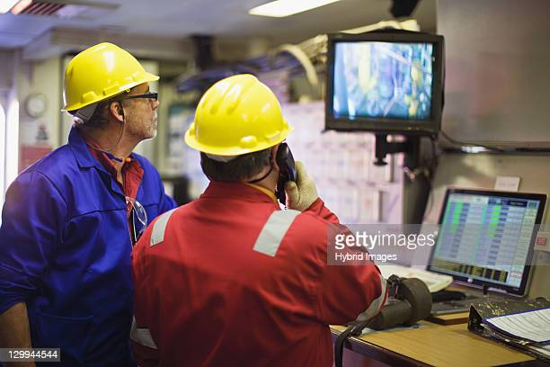 workers watching security cameras - oil worker stock pictures, royalty-free photos & images
