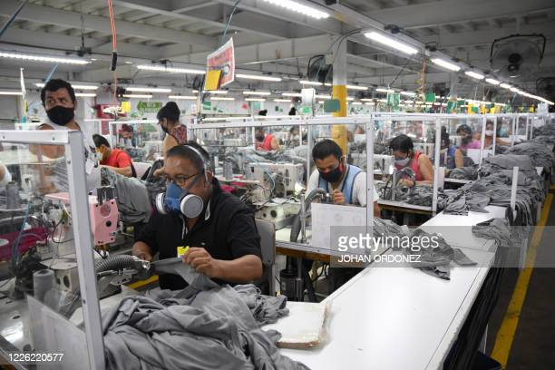 Workers wear face masks as a preventive measure against the spread of the novel coronavirus COVID19 at the textile plant KPTextil in San Miguel...