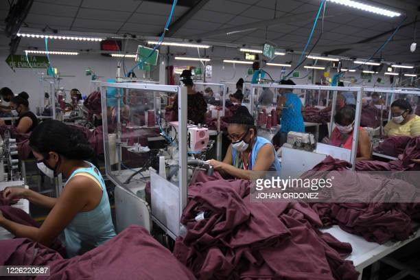 Workers wear face masks as a preventive measure against the spread of the novel coronavirus COVID-19, at the textile plant K.P.Textil in San Miguel...