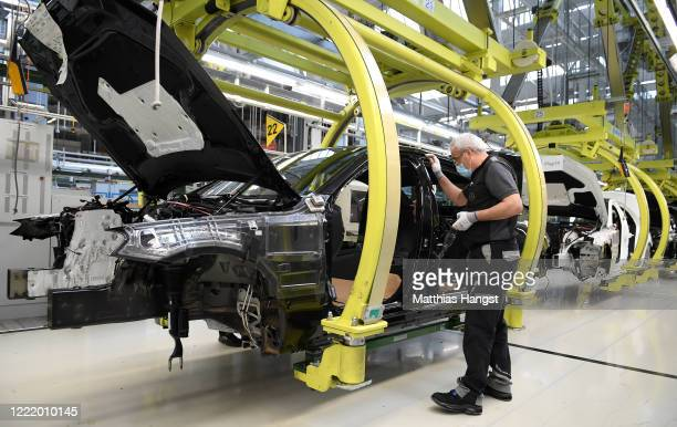 Workers wear protective face masks as they assemble cars at the Mercedes-Benz factory following the resumption of automobile production this week...