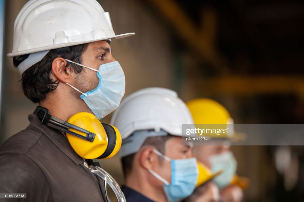 Workers wear protective face masks for safety in machine industrial factory. : Stock Photo