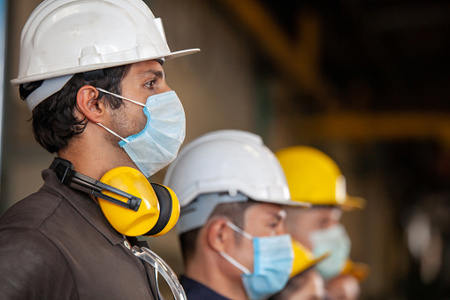 Workers wear protective face masks for safety in machine industrial factory. 1216223743