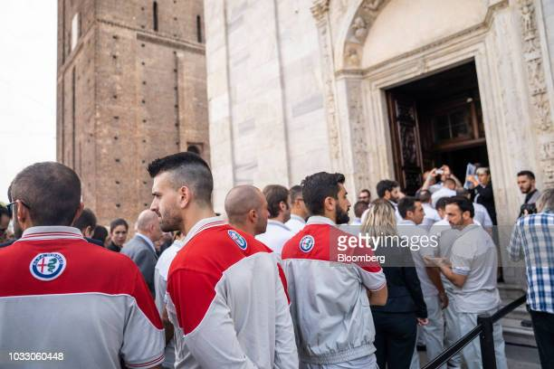 Workers wearing Alfa Romeo uniforms line up to attend a memorial service for former Fiat Chrysler Automobiles NV chief executive officer Sergio...