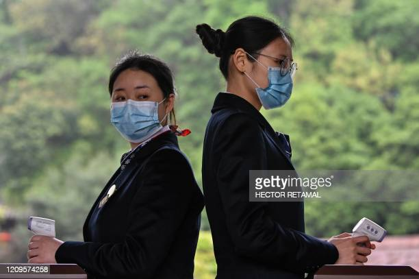 Workers wearing face masks hold thermometer gun scanners to check the temperature of visitors during a media tour to Yellow Crane Tower in Wuhan, in...