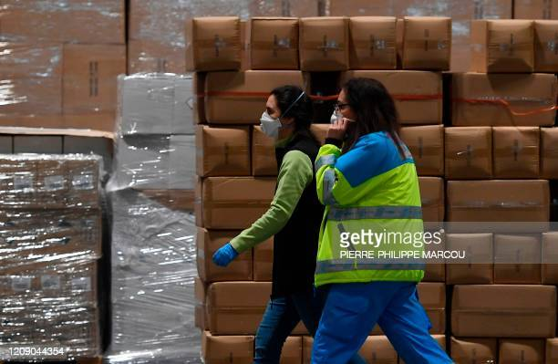 Workers wearing face masks walk by boxes of medical aid at the Ifema convention and exhibition centre in Madrid on April 03 2020 where a temporary...