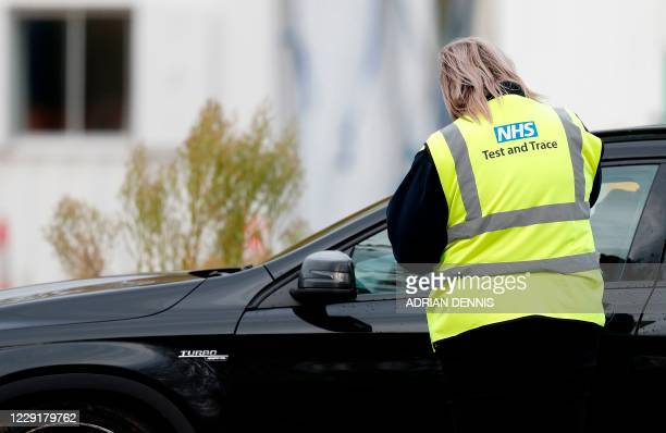 Workers wearing high-vis jackets with an NHS Test and Trace logo on, advises drivers attending a novel coronavirus COVID-19 drive-in testing facility...