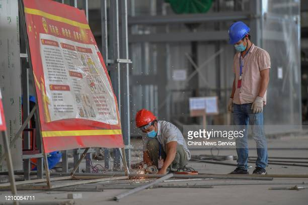 Workers wearing masks are seen at the construction site of the Haikou Meilan International Airport, one of the major projects of the China Pilot Free...