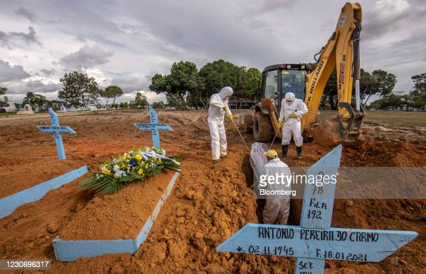 Workers wearing personal protective equipment lower the casket of a Covid-19 victim into a grave at a cemetery in Manaus, Brazil, on Tuesday, Jan....