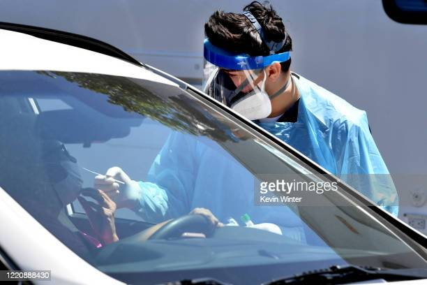 Workers wearing personal protective equipment perform drive-up COVID-19 testing administered from a car at Mend Urgent Care testing site for the...