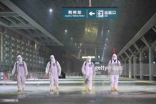 Workers wearing personal protective equipment spray disinfectant at Jingzhou Railway Station during the 40-day Spring Festival travel rush on...