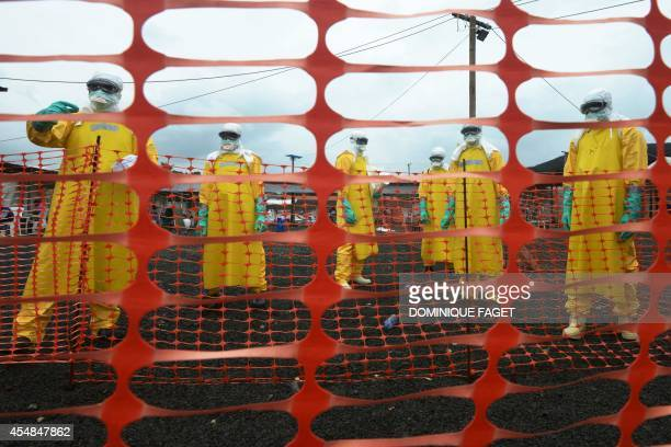 Workers wearing Personal Protective Equipment stand inside the contaminated area at the Elwa hospital runned by Medecins Sans Frontieres on September...