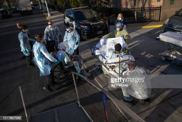 Workers wearing personal protective equipment , tend to COVID-19 patients arriving to the Montefiore Medical Center Wakefield Campus on April 06,...