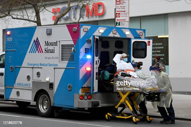 EMS workers wearing PPE load a COVID19 patient into an ambulance in front of a CityMD amid the coronavirus pandemic on April 12 2020 in New York City...