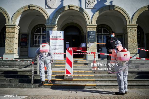 Workers wearing protective clothes disinfect entrance of the Town Hall in Kranj, Slovenia, on March 23, 2020 amid concerns over the spread of the...