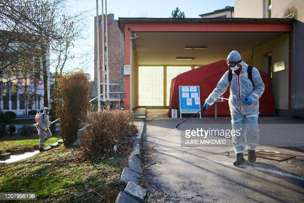 Workers wearing protective clothes disinfect one of the entrances at the Community Health Centre in Kranj, Slovenia, on March 23, 2020 amid concerns...