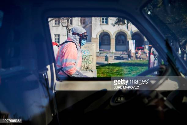 Workers wearing protective clothes disinfect one of the parks in Kranj, Slovenia, on March 23, 2020 amid concerns over the spread of the COVID-19...