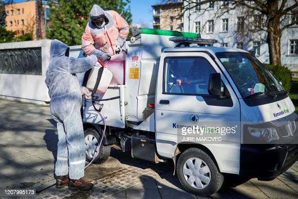 Workers wearing protective clothes prepare to disinfect one of the parks in city centre of Kranj, Slovenia on March 23, 2020 amid concerns over the...