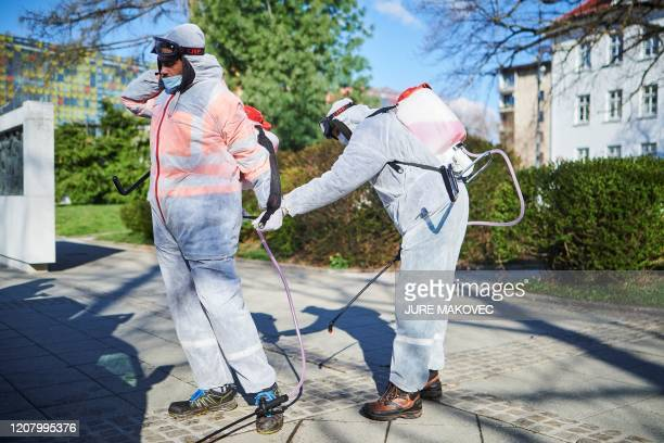 Workers wearing protective clothes prepare to disinfect one of the parks in city centre of Kranj, Slovenia, on March 23, 2020 amid concerns over the...
