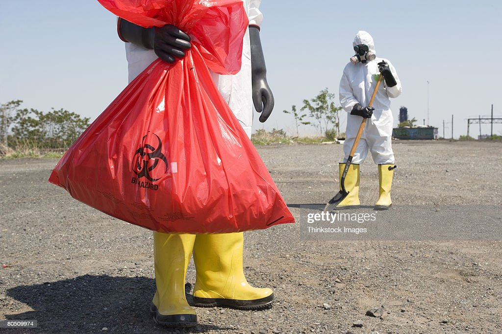 Workers wearing protective clothing removing hazardous waste : Stock Photo