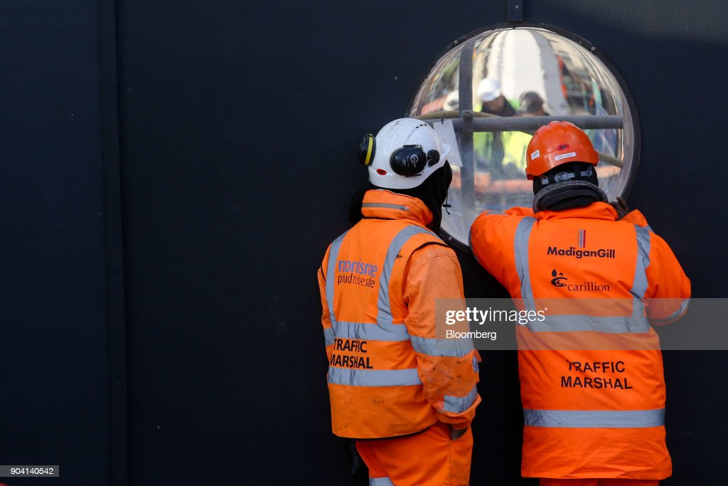 Workers wearing protective clothing with the logo of building contractor Carillion Plc, MadiganGill Ltd. and Morrisroe UK Ltd., view other workers on site through a porthole on a construction site in London, U.K., on Wednesday, Jan. 10, 2018. U.K. ministers are said to have met over the possible demise of Carillion, according to the Financial Times, without saying where it got information. Photographer: Luke MacGregor/Bloomberg via Getty Images