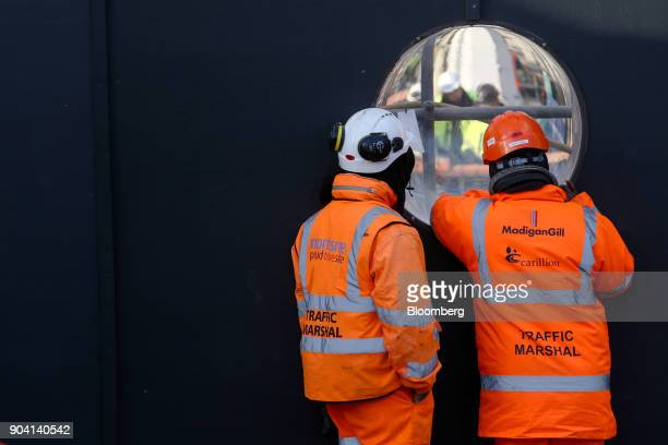 Workers wearing protective clothing with the logo of building contractor Carillion Plc MadiganGill Ltd and Morrisroe UK Ltd view other workers on...