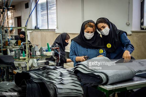 Workers wearing protective face masks cut denim cloth during the manufacture Iranian brand clothing, including Koi designed garments, at a factory on...