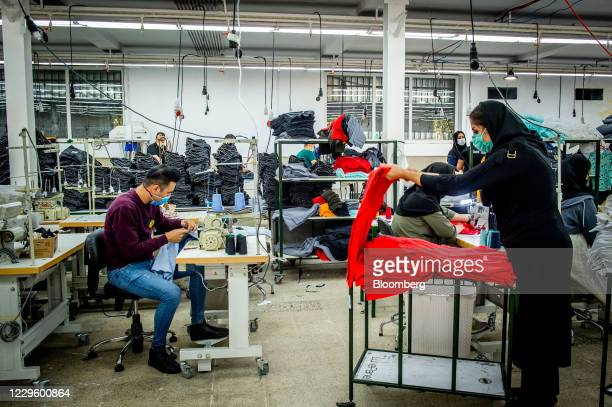 Workers wearing protective face masks manufacture Iranian brand jeans, including Koi designed garments, at a clothing factory on the outskirts of...