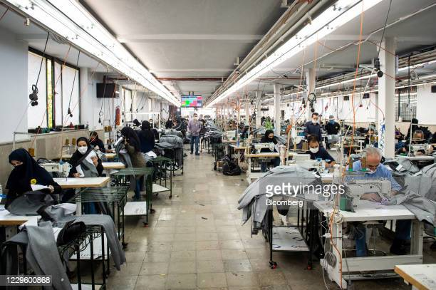 Workers wearing protective face masks manufacture Iranian brand jeans, including Koi designed garments, at a factory on the outskirts of Tehran,...