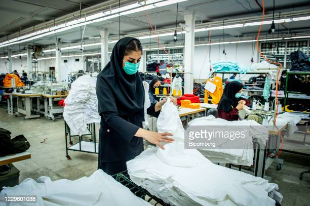 Workers wearing protective face masks manufacture Iranian brand clothing, including Koi designed garments, at a factory on the outskirts of Tehran,...