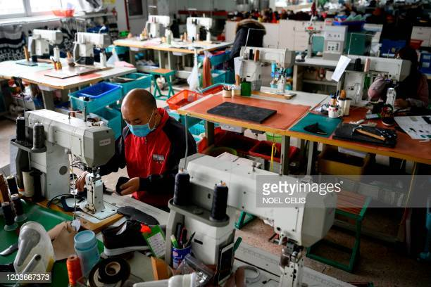 Workers wearing protective facemasks as a preventive measure against the COVID-19 coranavirus, sew shoe parts at the Zhejiang Xuda Shoes Co. Factory...
