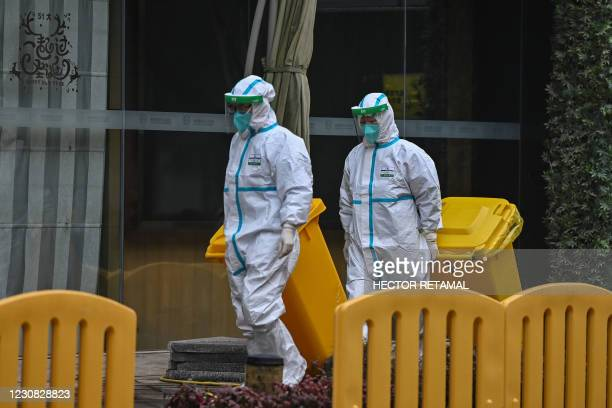 Workers wearing protective gear are seen in the compounds of The Jade Boutique Hotel, where members of the World Health Organization team...
