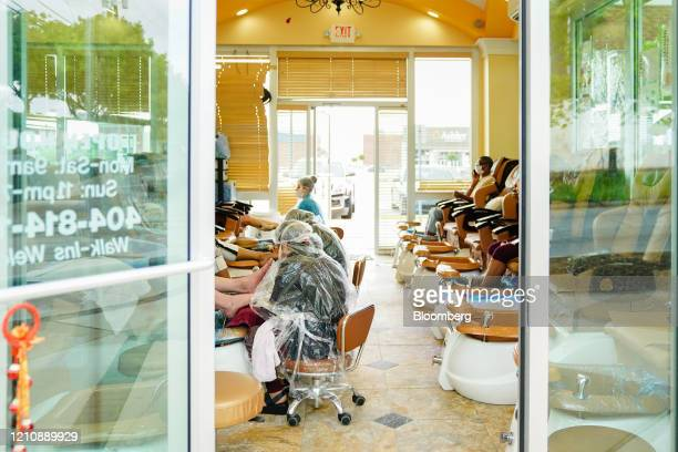 Workers wearing protective gear give customers pedicures at a nail salon in Atlanta Georgia US on Friday April 24 2020 Georgia's hair salons tattoo...