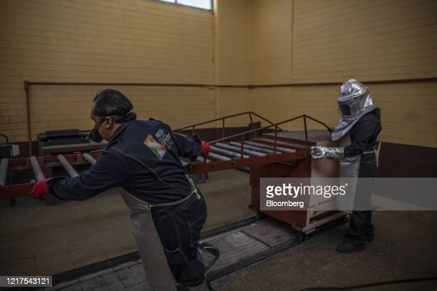 Workers wearing protective gear move a conveyor belt from an incineration oven at the municipality crematorium in Nezahualcoyotl Mexico on Thursday...