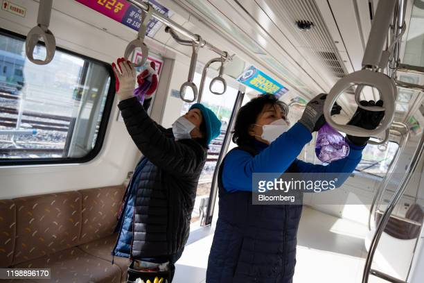 Workers wearing protective mask spray disinfectant onto handrails of a subway train operated Gimpo Goldline Co. In Gimpo, Gyeonggi Province, South...