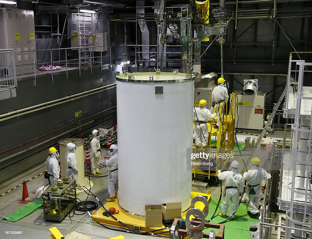 Workers wearing protective suits and masks check a transport container, front, and a crane in preparation for the removal of spent nuclear fuel rods from the spent fuel pool inside the building housing the No. 4 reactor at Tokyo Electric Power Co.'s (Tepco) Fukushima Dai-ichi nuclear power plant in Okuma, Fukushima Prefecture, Japan, on Thursday, Nov. 7, 2013. Tepco, which returned to profitability in its first-half earnings report on Oct. 31, is handling an estimated 11 trillion yen ($112 billion) cleanup of the nuclear plant wrecked by an earthquake and tsunami in 2011. Photographer: Kimimasa Mayama/Pool via Bloomberg