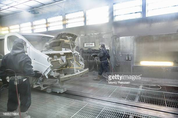 Workers wearing protective suits and masks spray painting van bodies in car factory