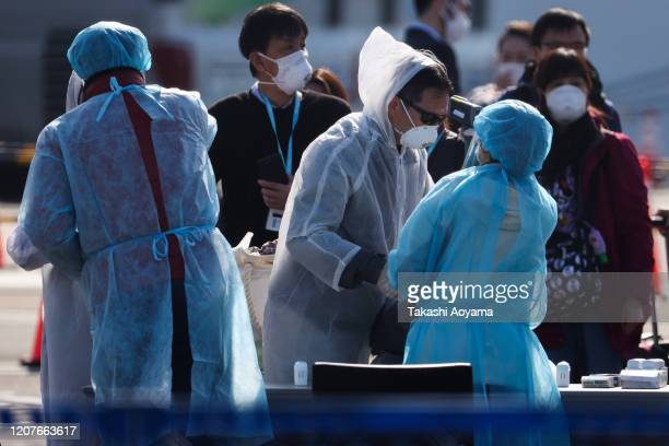 Workers wearing protective suits check the temperature of passengers before they ride a bus near the quarantined Diamond Princess cruise ship at the...