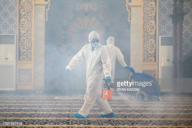 Workers wearing protective suits spray disinfectant at Suri Seri Begawan Raja Pengiran Anak Damit Mosque in an effort to counter the spread of the...