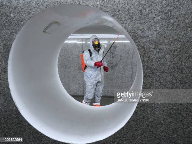 Workers wearing protective suits spray disinfectant at the Centrum subway station in Warsaw on April 6, 2020.