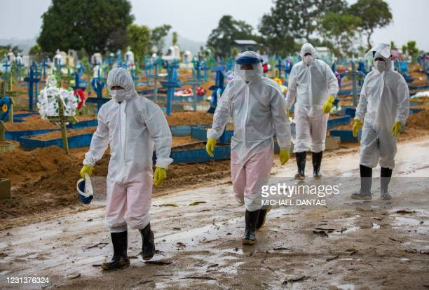 Workers wearing protective suits walk past the graves of COVID-19 victims at the Nossa Senhora Aparecida cemetery, in Manaus, Brazil, on February 25,...